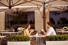 Happy married couple is on a honey moon, having brunch in nice cafe with modern interior, light summer terrace with green nice pla Royalty Free Stock Photo