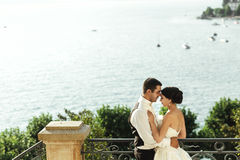 Happy married couple husband and whife hugging at stone balcony Stock Photos