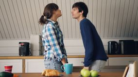 Happy married couple husband and wife are dancing in kitchen of cozy house hugging, laughing and kissing enjoying. Relationship and good mood. Youth and modern stock footage