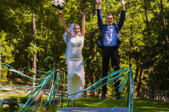 Happy married couple jumping on bridge Royalty Free Stock Images