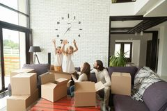 Happy couple with kids playing packing unpacking in living room Stock Photos