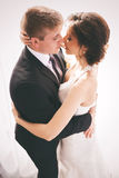 Happy married couple kissing in sunlight Stock Images