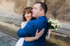 Happy married couple looking together towards the future near brown wall of old church, close-up.  Royalty Free Stock Photo