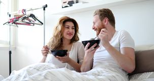 Happy married couple being romantic in bed sharing cereal Royalty Free Stock Images