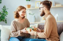 Happy married couple man and woman give a gift for holiday stock images