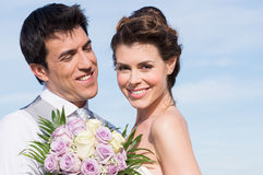 Happy Married Couple. Portrait Of Happy Married Young Couple Holding Bouquet Royalty Free Stock Photography