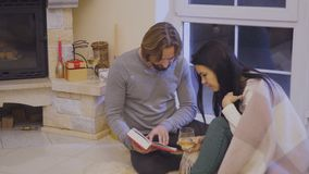Happy married couple read book relaxing near fireplace. Married couple sits on floor near fireplace and relaxing with book. Husband read the book to his wife stock video footage