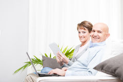 Happy married couple relaxing at home. Happy married middle-aged couple relaxing at home on the weekend sitting on a sofa browsing the internet on a tablet and Stock Photos