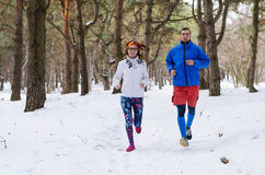 Happy married couple running around in winter forest. Royalty Free Stock Photography