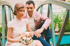 Happy married couple sitting on bridge Stock Image