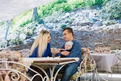 A happy married couple is sitting in a cafe and enjoying this time. They play with their child, he smiles. stock photography