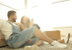 Happy married couple sitting on the carpet in a new apartment. Stock Photos
