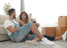 Happy married couple sitting on the carpet in a new apartment. Royalty Free Stock Photo