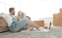 Happy married couple sitting on the carpet in a new apartment. Royalty Free Stock Images