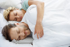 Happy married couple sleeping together on bed Stock Photography