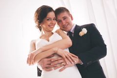 Happy married couple standing in sunlight Stock Photography