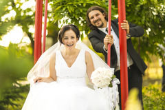 Happy married couple on their wedding day. Happy bride in a cradle swinged by the groom Royalty Free Stock Images