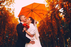 Happy married couple under umbrella Stock Images