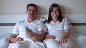 Happy married couple watching TV. Husband turned on comedy program and laughs with a contagious laugh along with his wife lying in bed stock footage