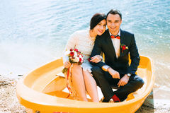 Happy married couple in yellow boat on sand Royalty Free Stock Photos
