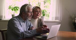 Happy married elderly couple using laptop sit at table indoor