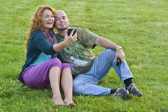 Happy married man and woman sitting on grass Stock Photography