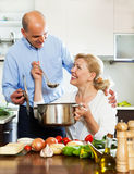 Happy married mature couple cooking in kitchen Royalty Free Stock Photo