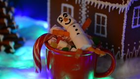 The happy marshmallow snowman in mag, hand-made eatable gingerbread house, snow decoration stock video