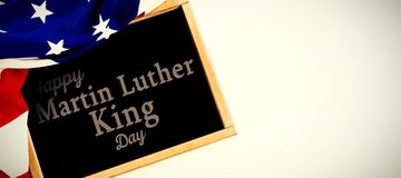 Composite image of happy martin luther king day. Happy Martin Luther King day against american flag and slate on table stock illustration