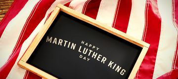 Composite image of happy martin luther king day. Happy Martin Luther King day against american flag with slate on wooden table stock photos