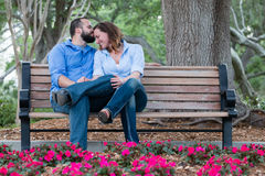 Happy Matching Couple in Garden. A couple wearing matching button down shirts sitting happily on a bench while he kisses her forehead royalty free stock image