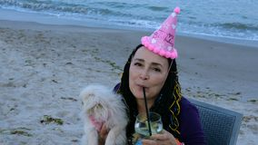 Happy mature adult woman caucasian ethnicity in a birthday cap with her dog - a white Pekingese. She drinking a cocktail on the seashore against the backdrop stock video footage