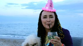 Happy mature adult woman caucasian ethnicity in a birthday cap with her dog - a white Pekingese. She drinking a cocktail on the seashore against the backdrop stock video