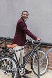 Happy mature african american man. With bike on parking for bicycles stock images