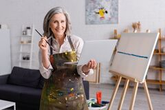 Free Happy Mature Artist Holding Paintbrush And Royalty Free Stock Photo - 217216675