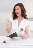 Happy mature assistant with thumb up at desk. Stock Images
