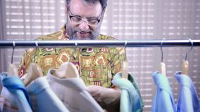 Happy mature bearded man shopping in a second-hand shop. Bearded mature man chooses a shirt hanging on clothes rail in a department store or second-hand shop. He stock video