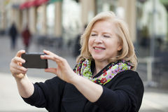 Happy Mature beautiful blonde woman photographed on a cell phone Stock Photos