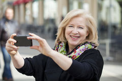Happy Mature beautiful blonde woman photographed on a cell phone Royalty Free Stock Photos