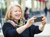 Happy Mature beautiful blonde woman photographed on a cell phone Royalty Free Stock Image