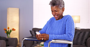 Happy Mature black woman texting on smartphone Royalty Free Stock Images