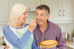 Happy mature blonde feeding pie to husband Stock Photography