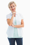 Happy mature blonde thinking with hand on chin Royalty Free Stock Photography