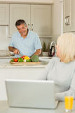 Happy mature blonde using laptop talking with husband Royalty Free Stock Photography