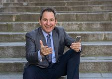 Happy mature business entrepreneur man sitting outdoors urban stairs working and using smart phone. Happy middle aged businessman on smart phone checking emails royalty free stock image