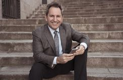 Happy mature business entrepreneur man sitting outdoors urban stairs working and using smart phone. Happy middle aged businessman on smart phone checking emails stock image