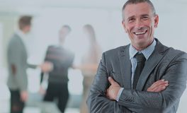 Happy mature business man looking at camera with satisfaction at office. Portrait of a mature business man Royalty Free Stock Photo