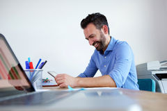 Happy mature business man sitting at his desk and using digital tablet. Side portrait of happy mature business man sitting at his desk and using digital tablet stock image