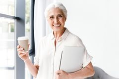 Happy mature business woman holding laptop stock image