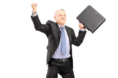 Happy mature businessman with briefcase gesturing happiness Stock Photos